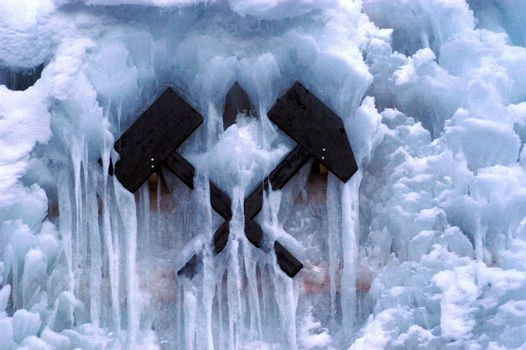 crossed hammer and pickaxe, mining symbol covered in snow and ice