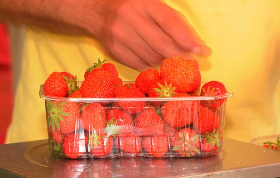 fresh red strawberries in a plastic box on the market
