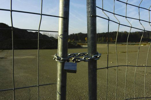 industrial crisis symbolized by a gate locked with a chain