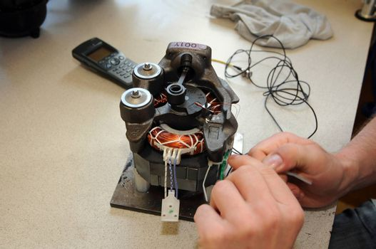 an engineer is working with his hands on an electric motor