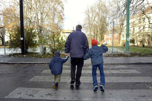 father with his two children crossing the street on a crosswalk
