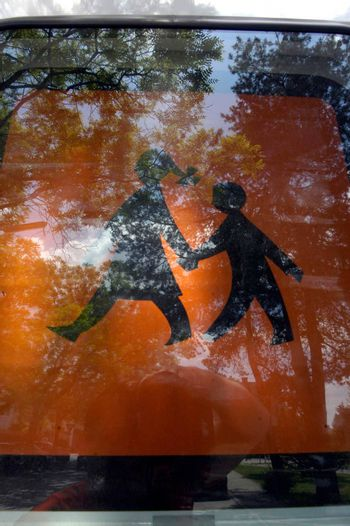 orange children crossing sign at a school bus behind the window