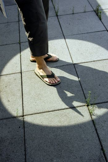 man wearing flip flop sandals on the sidewalk in the city, footwear for summer