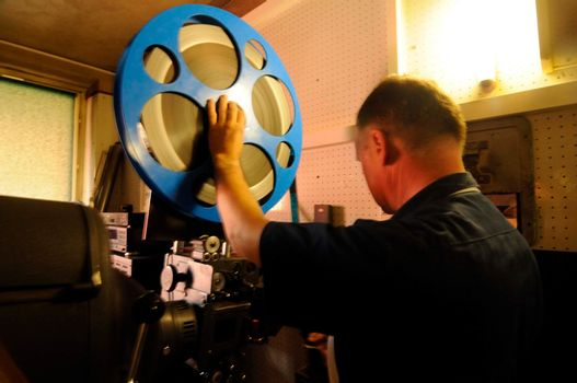 film projectionist in a cinema with film reel and projector