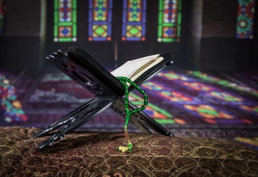 Holy muslim koran on eastern carpet in mosque. Islamic Book Koran with rosary