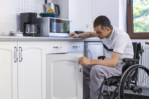 Young Handicapped Man Sitting On Wheelchair In Kitchen. Focus on his face.