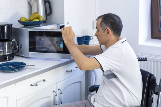 Young Man in Whellchair Using Microwave Oven For Baking In Kitchen. Focus on his hand.
