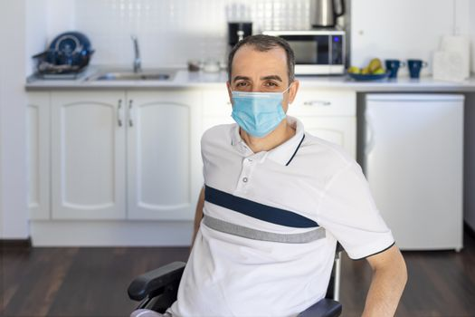 Smiling Young Handicapped Man Sitting On Wheelchair In Kitchen.  Young man wearing face mask sitting infront of kitchen. Focus on his face.