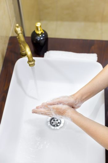 Woman washing and disinfecting hands with soap and hot water as part of coronavirus prevention and protection protocols; stop spreading covid-19 hygiene protocols