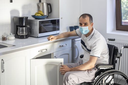 Smiling Young Handicapped Man Sitting On Wheelchair In Kitchen.  Young man wearing face mask sitting in front of kitchen. Focus on his face.