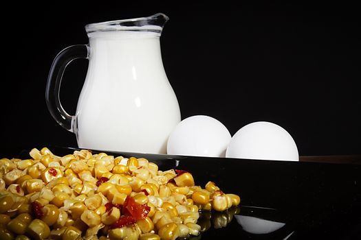 Corn and milk in a jug on a black reflective surface