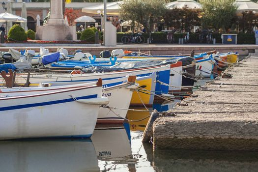 BARDOLINO, ITALY 16 SEPTEMBER 2020: Colored boats moored on Bardolino port in Italy