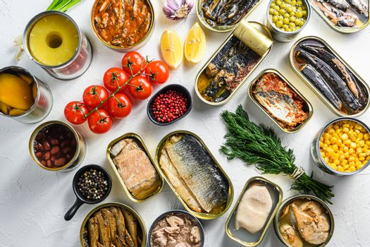 Different canned conserve products in tin cans. with fresh organic ingridients Saury, mackerel, sprats, sardines, pilchard, squid, tuna pinapple, corn, peas, mango , beans, over white textured background top view