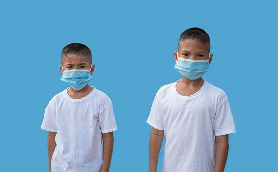 Two boy wearing a protective mask on a blue background. New normal concept.
