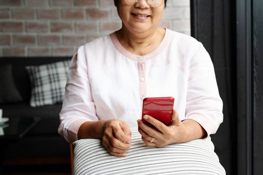 smiling senior woman using mobile phone while sitting on sofa at home