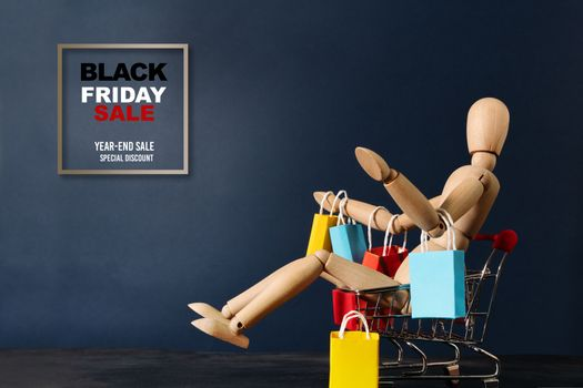 Black Friday sale, wooden doll sitting on shopping cart with shopping bag