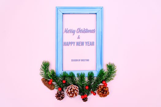 Christmas pine tree and photo frame with xmas decoration on pink background
