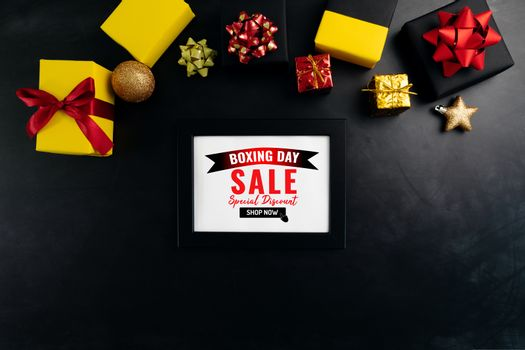 Boxing day sale with Christmas present and xmas decoration on black background
