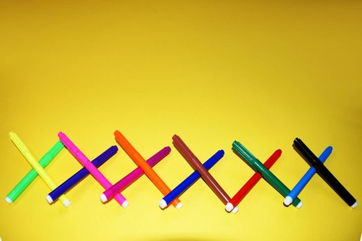 multicolored markers on a yellow background close-up