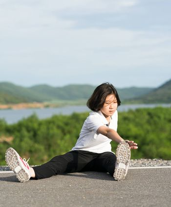 Woman runner doing exercises and warm up preparing for jogging outdoor