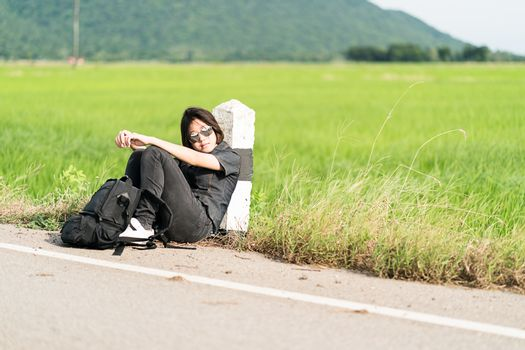 Young asian woman short hair and wearing sunglasses sit with backpack hitchhiking along a road wait for help in countryside Thailand