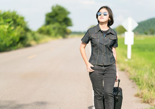 Young asian woman short hair and wearing sunglasses with luggage hitchhiking along a road in countryside Thailand