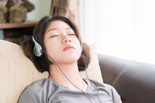 Close up young asian woman short hair listening music from mobile phone on the couch