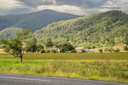 Bright sunlight passing over a roadside country property with a mountain background