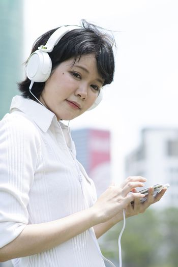 Happy asian woman listening to music on mobile phone in garden.