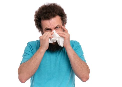 Crazy bearded Man with funny Curly Hair has a runny nose, isolated on white background. Sick guy with paper napkin blowing nose. People, healthcare, cold or Allergy concept.