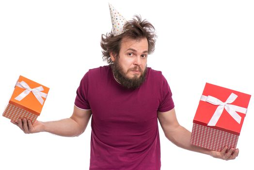 Crazy bearded Man with funny Haircut in birthday cap, isolated on white background. Confused guy holding gift boxes. Holidays concept.