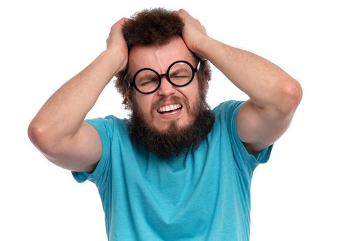 Crazy bearded Man with funny Curly Hair, in eye Glasses, suffering from headache. Upset unhappy Sick guy squeezing head with hands, writhing in pain. People, healthcare, stress or migraine concept