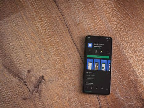Lod, Israel - July 8, 2020: Signal Private Messenger app play store page on the display of a black mobile smartphone on wooden background. Top view flat lay with copy space.