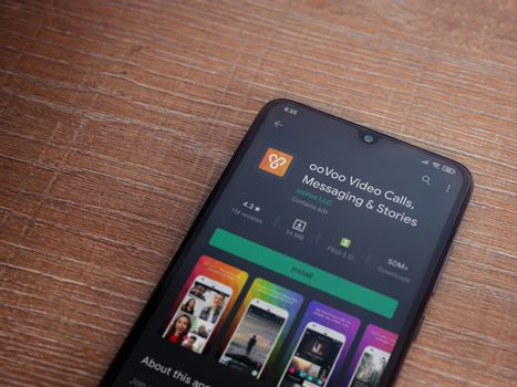 Lod, Israel - July 8, 2020: ooVoo app play store page on the display of a black mobile smartphone on wooden background. Top view flat lay with copy space.