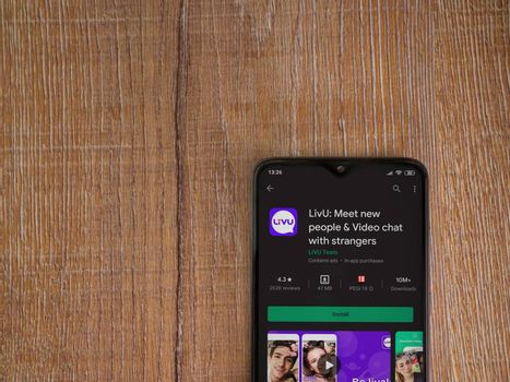 Lod, Israel - July 8, 2020: LiveU app play store page on the display of a black mobile smartphone on wooden background. Top view flat lay with copy space.