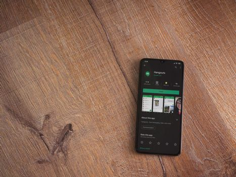Lod, Israel - July 8, 2020: Hanghouts app play store page on the display of a black mobile smartphone on wooden background. Top view flat lay with copy space.