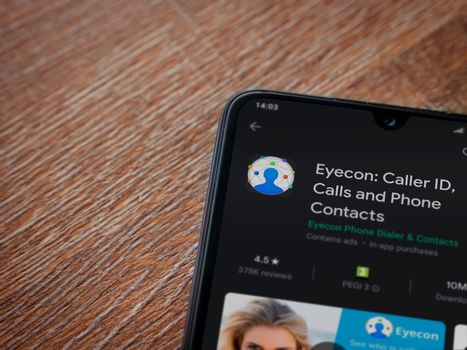 Lod, Israel - July 8, 2020: Eyecon app play store page on the display of a black mobile smartphone on wooden background. Top view flat lay with copy space.