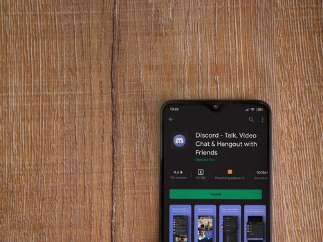 Lod, Israel - July 8, 2020: Discord app play store page on the display of a black mobile smartphone on wooden background. Top view flat lay with copy space.