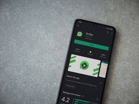 Lod, Israel - July 8, 2020: Scriby app play store page on the display of a black mobile smartphone on ceramic stone background. Top view flat lay with copy space.