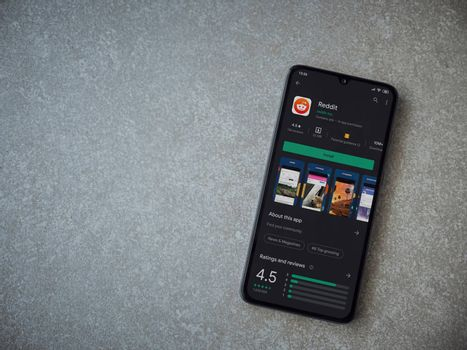 Lod, Israel - July 8, 2020: Reddit app play store page on the display of a black mobile smartphone on ceramic stone background. Top view flat lay with copy space.