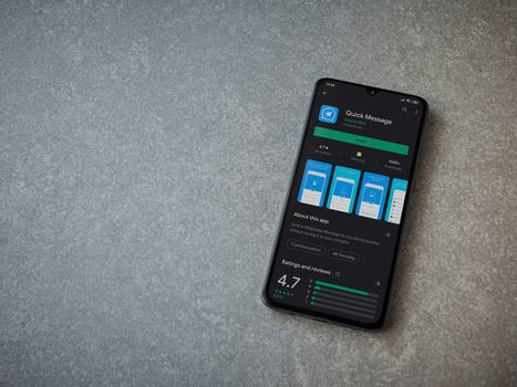 Lod, Israel - July 8, 2020: Quick Message app play store page on the display of a black mobile smartphone on ceramic stone background. Top view flat lay with copy space.