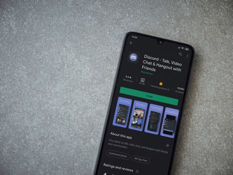 Lod, Israel - July 8, 2020: Discord app play store page on the display of a black mobile smartphone on ceramic stone background. Top view flat lay with copy space.