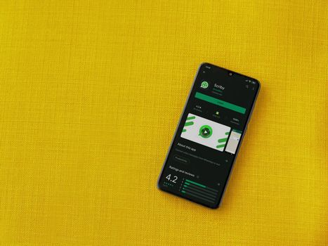 Lod, Israel - July 8, 2020: Scriby app play store page on the display of a black mobile smartphone on a yellow fabric background. Top view flat lay with copy space.