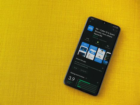 Lod, Israel - July 8, 2020: Me app play store page on the display of a black mobile smartphone on a yellow fabric background. Top view flat lay with copy space.