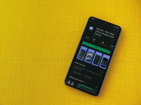 Lod, Israel - July 8, 2020: Discord app play store page on the display of a black mobile smartphone on a yellow fabric background. Top view flat lay with copy space.