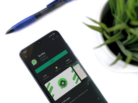 Lod, Israel - July 8, 2020: Modern minimalist office workspace with black mobile smartphone with Scriby app play store page on white background. Top view flat lay with copy space.