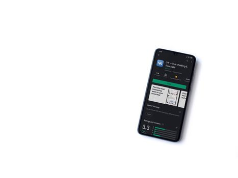 Lod, Israel - July 8, 2020: VK app play store page on the display of a black mobile smartphone isolated on white background. Top view flat lay with copy space.
