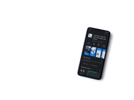 Lod, Israel - July 8, 2020: Truecaller app play store page on the display of a black mobile smartphone isolated on white background. Top view flat lay with copy space.