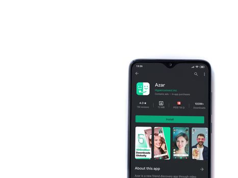 Lod, Israel - July 8, 2020: Azar app play store page on the display of a black mobile smartphone isolated on white background. Top view flat lay with copy space.