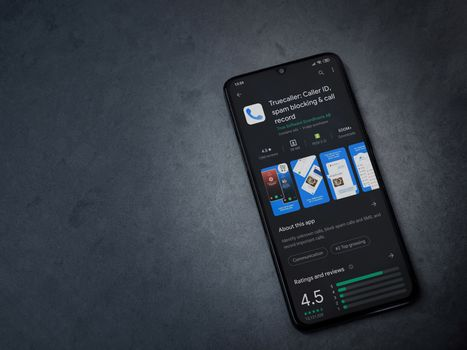 Lod, Israel - July 8, 2020: Truecaller app play store page on the display of a black mobile smartphone on dark marble stone background. Top view flat lay with copy space.